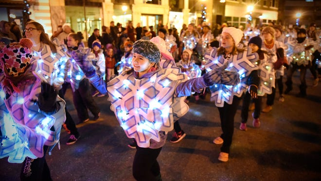 Dancers with Ms. Melinda's Dance Studio wave to the crowd Saturday during the Winter Nights and Lights Festival parade in downtown St. Cloud.