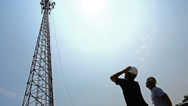 Sprint construction project manager Will Sylvester and Velex technician Ben Warner shield their eyes from the sun while a North Lynhurst Drive Sprint cell tower is updated near Indianapolis Motor Speedway, Thursday, July 2, 2015, Indianapolis, Ind.