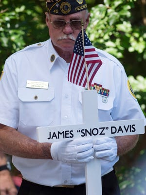 "Jim Hanley with the Henderson American Legion Post 40 Honor Guard carries the newest addition to the Central Park memorial cross display, James ""Snoz"" Davis's cross, at the Memorial Day service Monday morning. Davis died recently and was the last living member of the group responsible for starting the memorial cross display which honors all veterans who have died in Henderson County with a cross bearing their names."