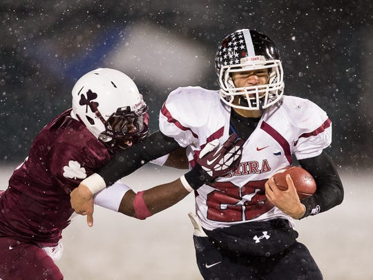 Eli Thomas, of Elmira, is brought down by Aquinas'