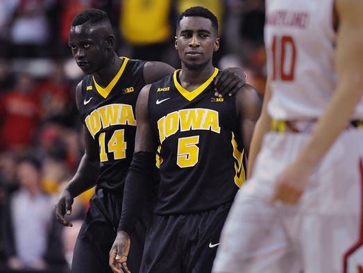 Iowa's Peter Jok, left, consoles Anthony Clemmons after