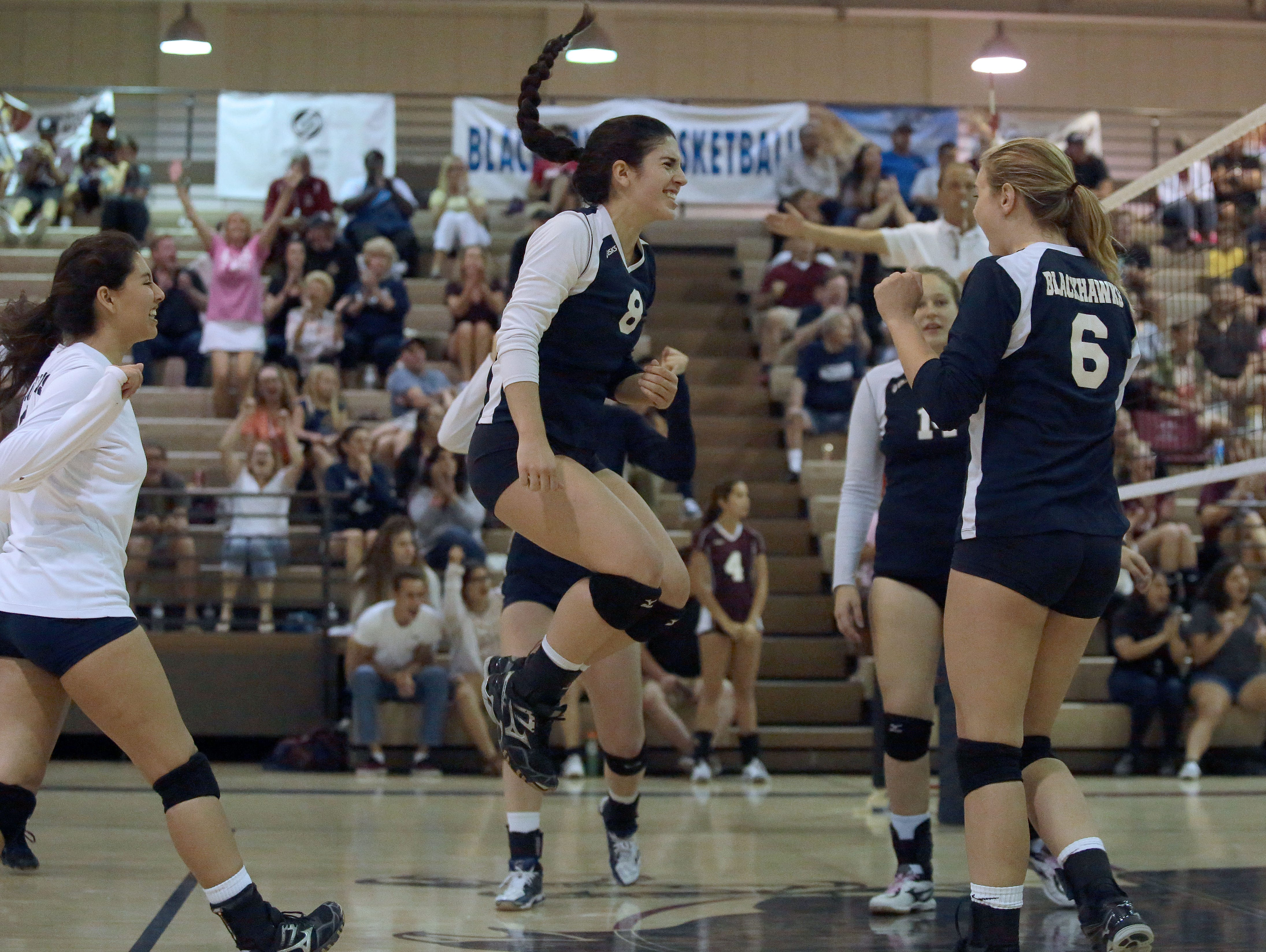 La Quinta volleyball players celebrate a hard point won from Palm Springs in the 3rd set against Palm Springs on Thursday. La Quinta won the match 3 sets to 1.