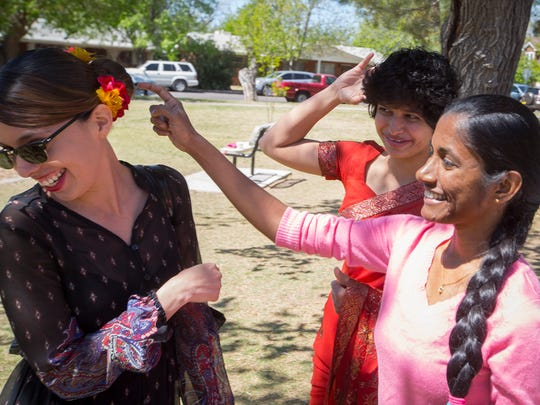 Luisa Valverde, left, representing Mexico and Rachel Jayah and Jayasinghage Ruchira Nirmali Perera, from Sri Lanka, discuss different hair styles during the Las Cruces International Festival at Pioneer Women's Park, April 2, 2016.