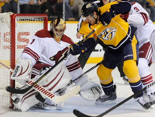 Nashville Predators center Craig Smith (15) tries to jam the puck past Phoenix Coyotes goalie Thomas Greiss (1) during the first period at Bridgestone Arena Thursday, April 10, 2014 in Nashville, TN.