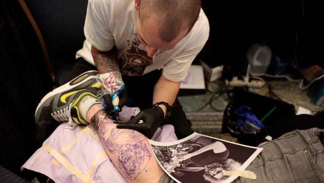 Brent Olson from Hesperia, Calif., tattoos a portrait of Jerry Garcia on the calf of Scott Hurlbert from Farmington Hills during the 2015 Motor City Tattoo Expo.