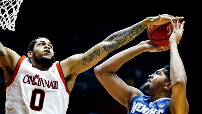 University of Memphis forward Dedric Lawson (right) is fouled by University of Cincinnati defender Quadri Moore while driving for a layup during first-half action at Fifth Third Arena in Cincinnati.