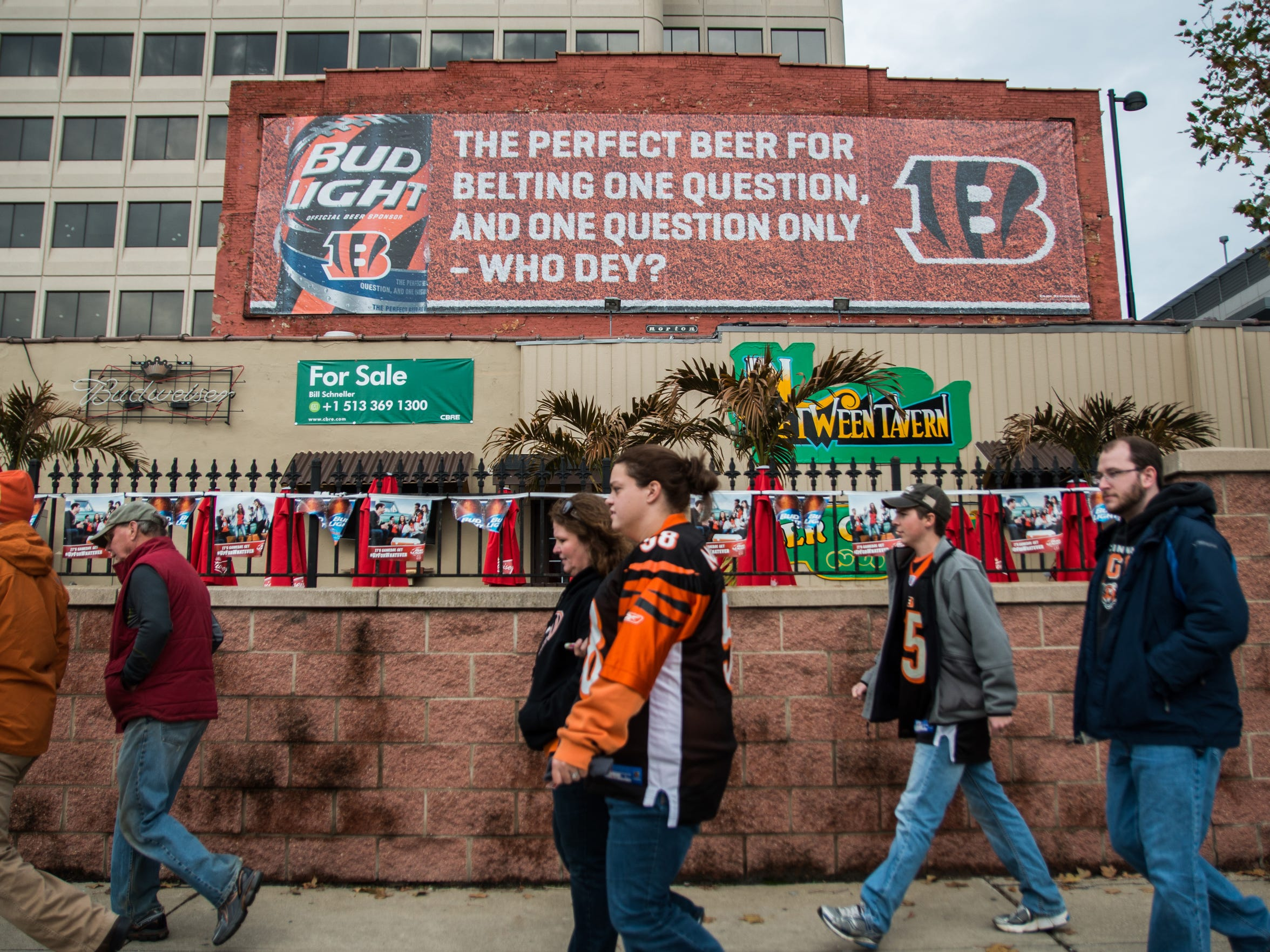 Bengals fans walk past a Who Dey Bud Light ad on Third
