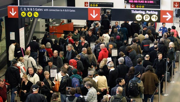 Travelers wait in a TSA security checkpoint line Dec.