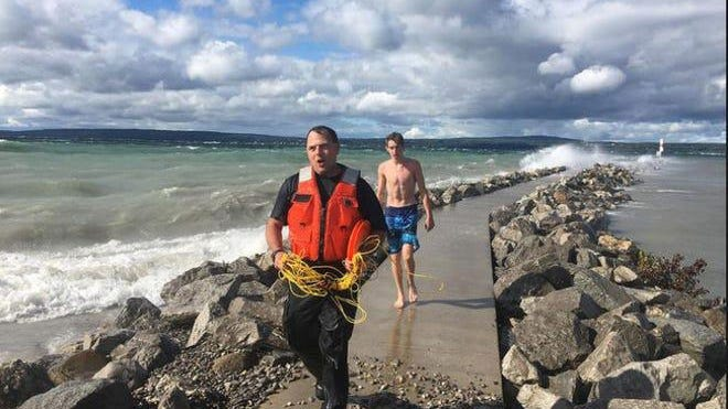 Petoskey Department of Public Safety officer Scoot Gosciak walks off the Petoskey breakwater Saturday after helping a teen get out of the water after being swept off the structure by high waves.