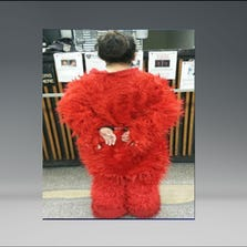 A woman dressed as Elmo is shown in handcuffs, after being arrested for allegedly aggressively seeking tips in Times Square.
