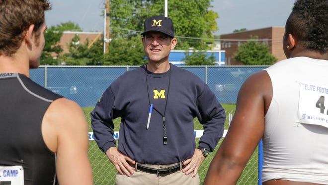 Michigan Coach Jim Harbaugh talks with campers at the Bishop Chatard High School Elite Football Camp in Indianapolis in June.