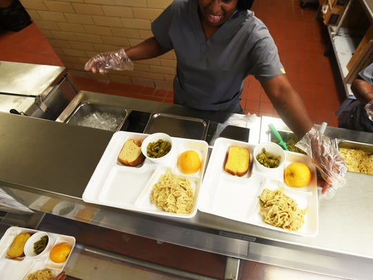 Shalonda Vinson serves lunch at Waller Elementary in