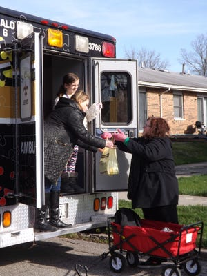 Jamie Julian from St. Clair EMS left, and Abigail Lathery help take bags of food collected from Daisy Girl Scout leader Lora Lathery during a food drive Tuesday in Liberty.