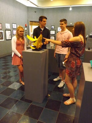 "Ashley Miller of Seton Catholic High School, right points to the ""Booming Banana"" sculpture made by Ben Grayson of Richmond High School, third from right, as Ashley Toschlog of Centerville High School, left, and Marshal Bane of Seton also chat about the award-winning piece in the All Wayne County High School Art Exhibition at Richmond Art Museum."