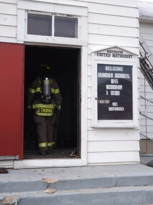 A firefighter enters Whitewater United Methodist Church after Sunday's fire.