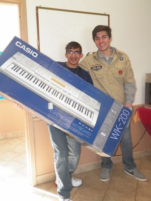 Boy Scout Elias Kotsis (right) and Jimmy Peters bring a keyboard into Amandla Crossing transitional housing.