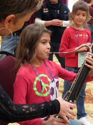 Jeanie Harnish teaches Kira Benton about playing the bassoon at a past Music for Families. This year's event is Saturday at the Saenger Theatre in downtown Pensacola.