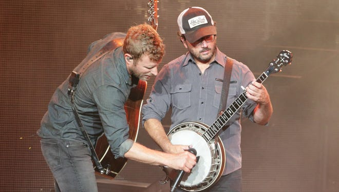 Dierks Bentley, left, provides added amplification for banjo player Tim Sergent during Saturday's show at Klipsch Music Center.
