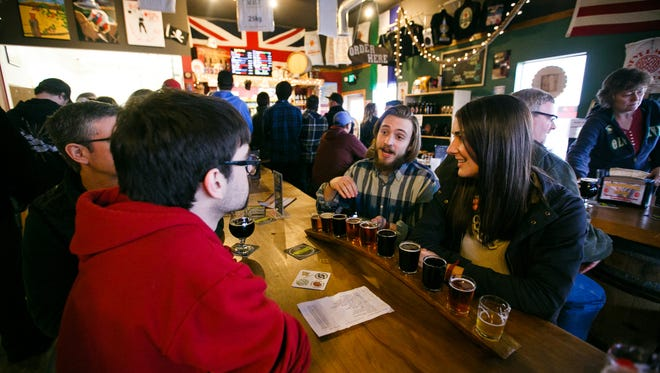(Right to left) Katie Baumann, Ian Metz and Will Baumann share a tasting flight at Santiam Brewing recently. The brewery will be pairing Girl Scout Cookies with beer on March 3.