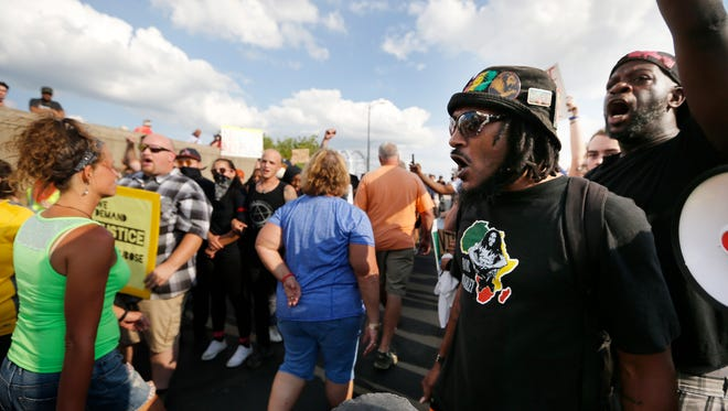 Ray Tensing supporters, center, make their way through demonstrators with Black Lives Matter: Cincinnati Monday July 24, 2017, at the Purple People Bridge. A small group with #TensingStrong prayed at the bottom of the bridge before walking across. Ray Tensing, the former University of Cincinnati cop, shot and killed Sam DuBose July 2015. Charges against him were dropped Monday after two hung juries. Black Lives Matter and other affiliated groups held a counter-rally also in support for justice for Sam DuBose.