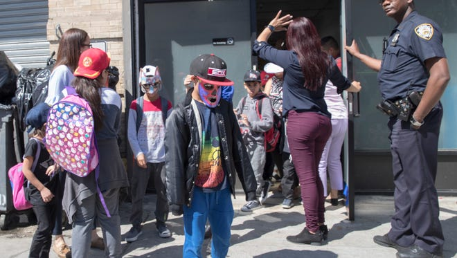A police officer stands guard as children wearing homemade masks are escorted as they leave the Cayuga Centers facility on June 21, 2018, in the East Harlem neighborhood of New York. Hundreds of migrant children separated from their parents by federal immigration officials are being cared for in the facility.