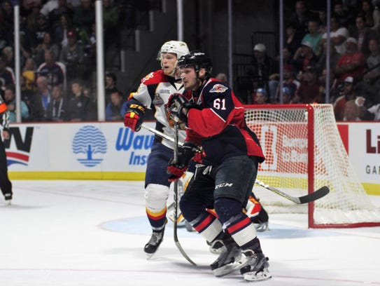 Luke Boka (61) of the Windsor Spitfires vies with an