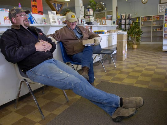 Kale Sandman, left, and Calvin Thomas hang out at the Sand Springs Store in Sand Springs in 2006. The town has a store, a church and a school.