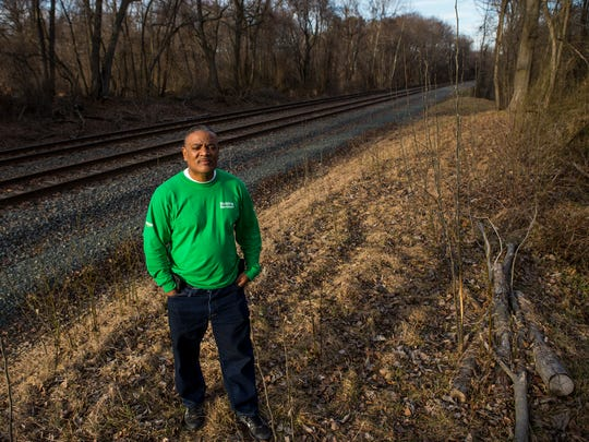 Reggie Ennis stands near the train tracks behind his home in New Castle on Tuesday afternoon. Ennis believes a long pattern of trains idling for hours on end on the tracks has caused damage to his home.