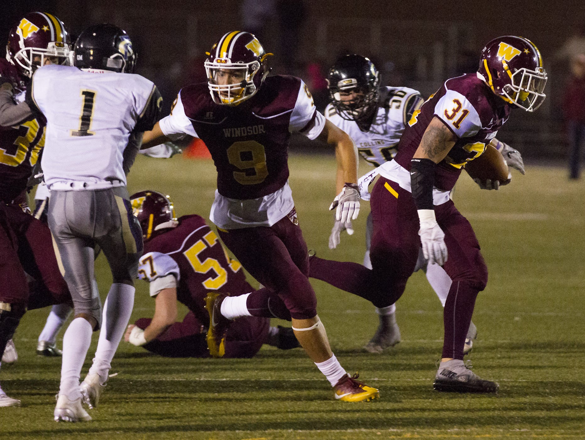 Windsor running back Corte Tapia (31), right, runs from the backfield Friday as teammates Jaedyn Traut (9) and Keller Kretchmer (30) block Fort Collins. The Wizards have qualified for the 4A playoffs to defend their title.