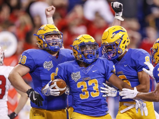 Carmel Greyhounds Jerome Halsell (33) and  teammates celebrate after scoring a touchdown against Center Grove in the Class 6A state title game Friday at Lucas Oil Stadium.