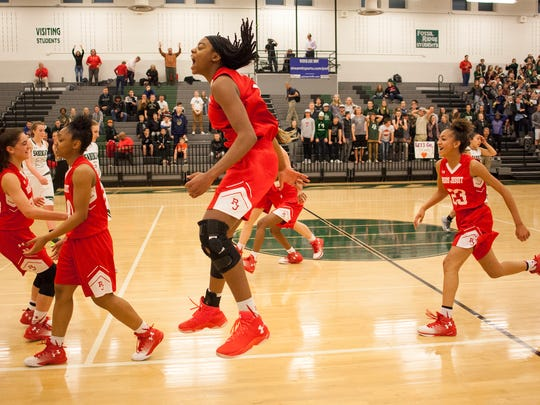 Regis Jesuit sophomore forward Francesca Belibi (1) leaps in celebration after defeating Fossil Ridge 49-45 Tuesday evening in a Class 5A Sweet 16 game.
