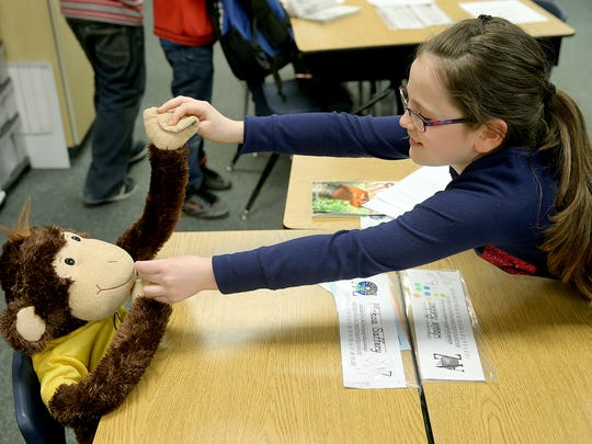 Gordon Elementary second gradet Josie Reber, 8, poses the arms of the monkey that represents her classmate, Makoa Saffery.