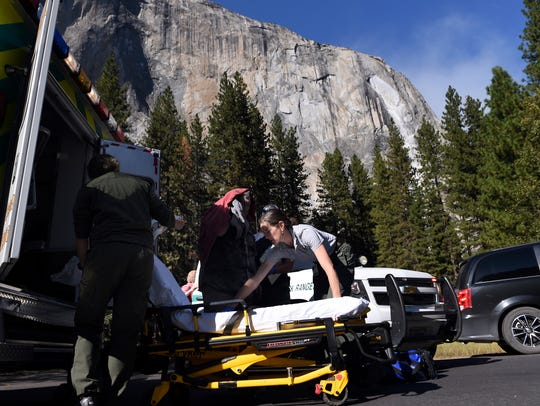 Emergency personnel prepare to care for an elderly