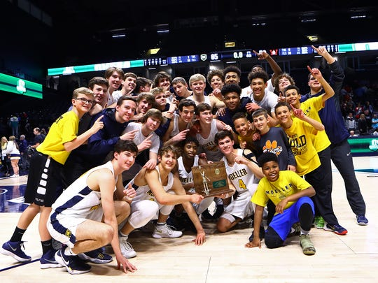 Moeller players and managers celebrate with the Regional