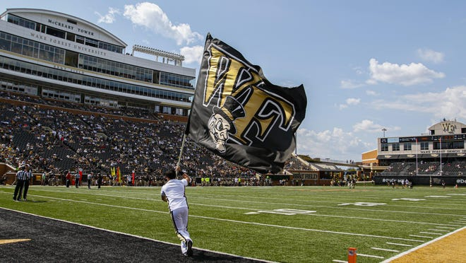 A Wake Forest cheerleader waves a flag during the Demon Deacons' home football game against Elon last September.