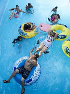 Electric City Water Park patrons make a chain in the lazy river Saturday. More than 600 people attended the water park to cool off from temperatures that reached the 90s.
