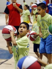 Ian Motolina, 6, took aim for a shot as more than a 100 youngsters warmed up in 2004 during Basketball in the Barrio.