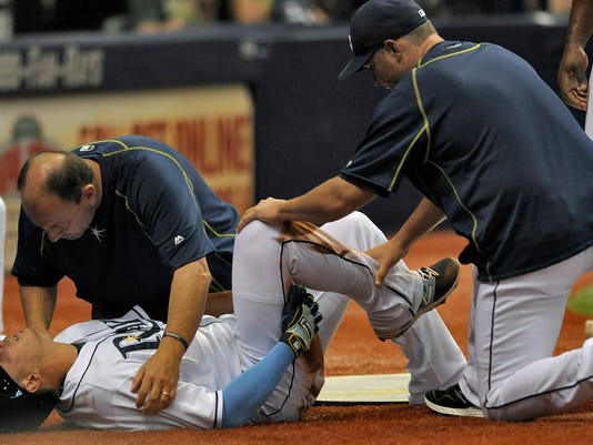 Tampa Bay Rays trainer Ron Porterfield, left, and manager Kevin Cash, right, attend to Asdrubal Cabrerra after he pulled up lame while scoring on Rene Rivera's two-run single during the second inning of a baseball game against the Houston Astros, Saturday, July 11, 2015, in St. Petersburg, Fla. (AP Photo/Steve Nesius)