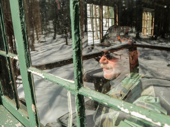 "Armas Ojaniemi, 60, of Bruce Crossing looks out the window of his cabin on March 19, 2017. ""It didnít take much to enjoy yourself out here, ""cause it's so peaceful,"" said Armas, who lives in tiny Bruce Crossing, the nearest town."