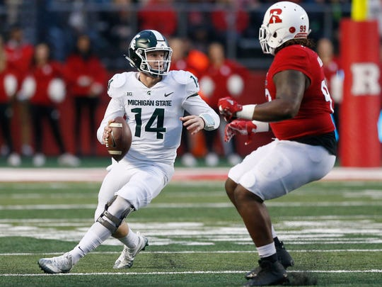 Michigan State quarterback Brian Lewerke (14) avoids the tackle of Rutgers defensive lineman Kevin Wilkins (99) during the first half of MSU's 40-7 win on Saturday, Nov. 25, 2017, in Piscataway, N.J.