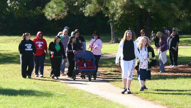 A group of friends walk in tribute to their lost loved ones Saturday at Southern Hills Park as part of the Out of the Darkness Walk in 2009.