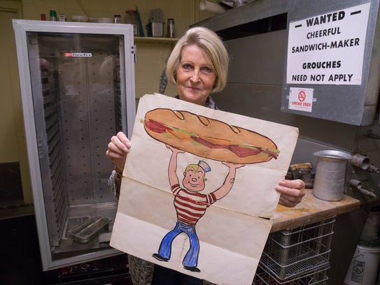 Sandy McPhail holds a logo made by her husband Dan,
