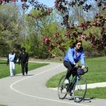 A bicyclist enjoys the River Trail near Potter Park Zoo.