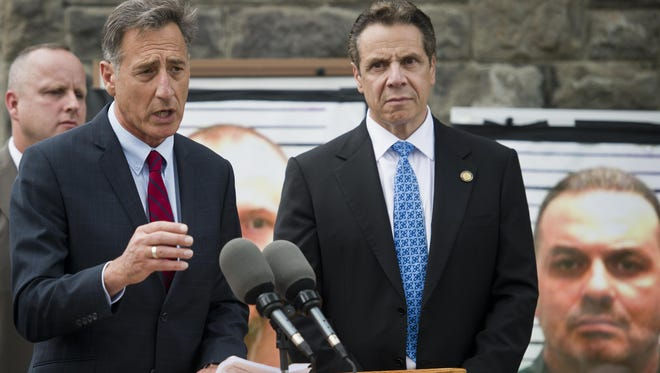 Vermont Gov. Peter Shumlin speaks at a news conference outside the Clinton Correctional Facility in Dannemora, N.Y., with New York Gov. Andrew Cuomo and Col. Tom L'Esperance, left, director of the Vermont State Police on Wednesday. A poster of one of the killers is on the right.