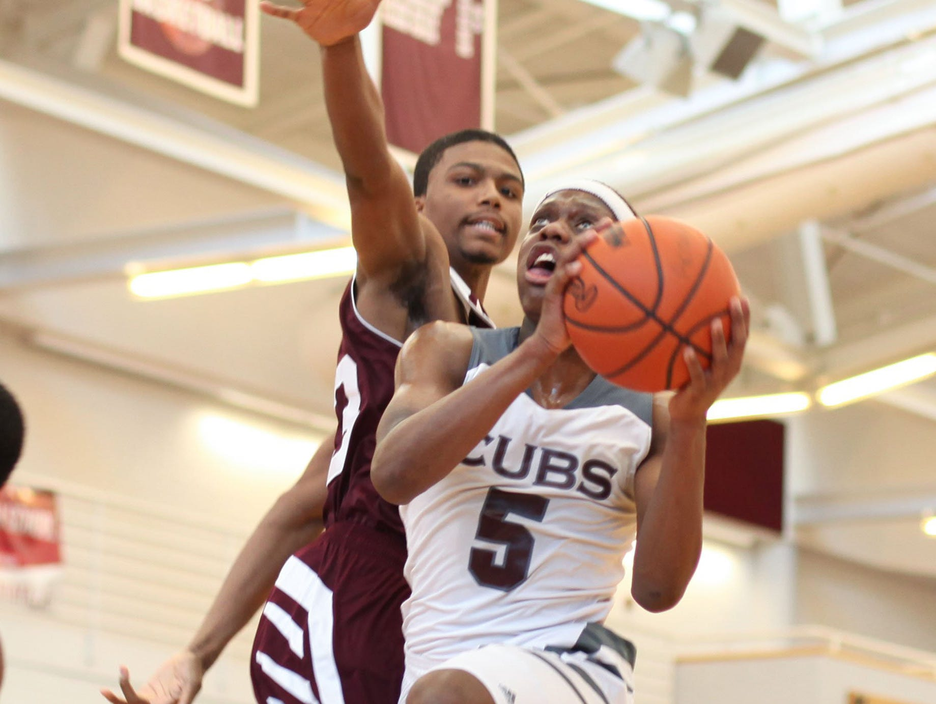 Renaissance's Daelyn Davis tries to block U-D Jesuit's Cassius Winston as he goes for a shot during a game.