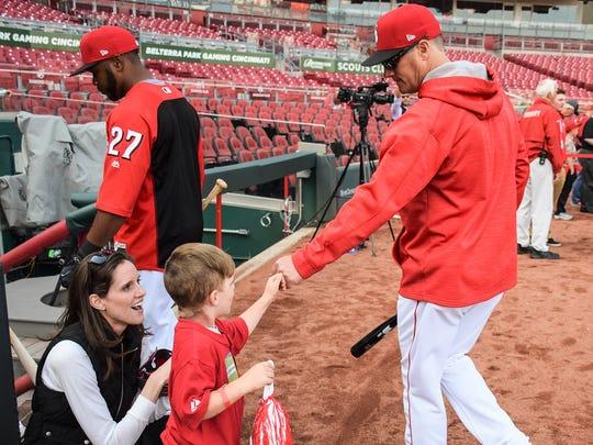 Cincinnati Reds catching coordinator Mike Stefanski (right) fist pumps a young fan.