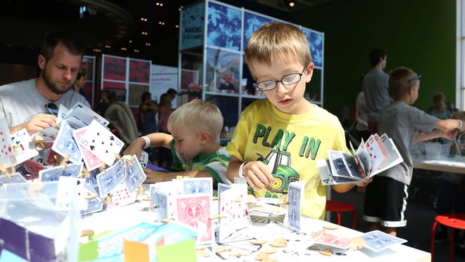 Kids build objects using playing cards at the Science Center of Iowa.