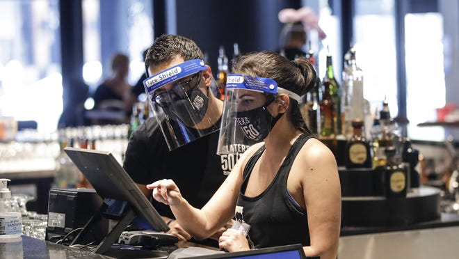 Bartenders were masks and face shields as they work at Slater's 50|50 in Wednesday, July 1, 2020, in Santa Clarita, Calif. Health experts at the local and federal level say that wearing just a face shield is not a suitable alternative to wearing a mask.