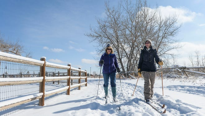 Susan Wang, right, and Becky Bryant cross-country ski in the snow accumulation from the weekend Monday, Feb. 23, 2015 near Spring Canyon Park in Fort Collins, CO.
