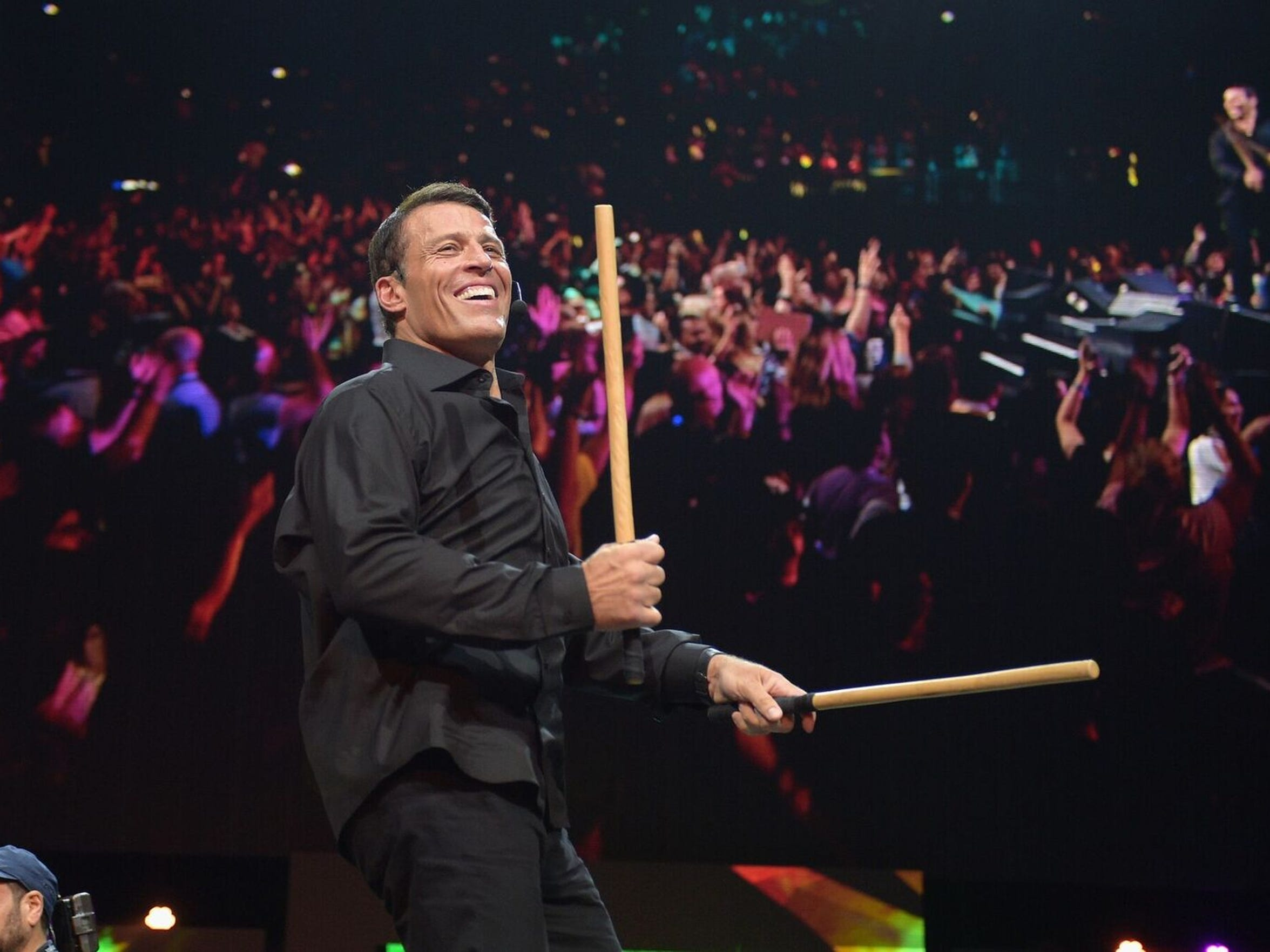Tony Robbins bangs sticks together at the start of